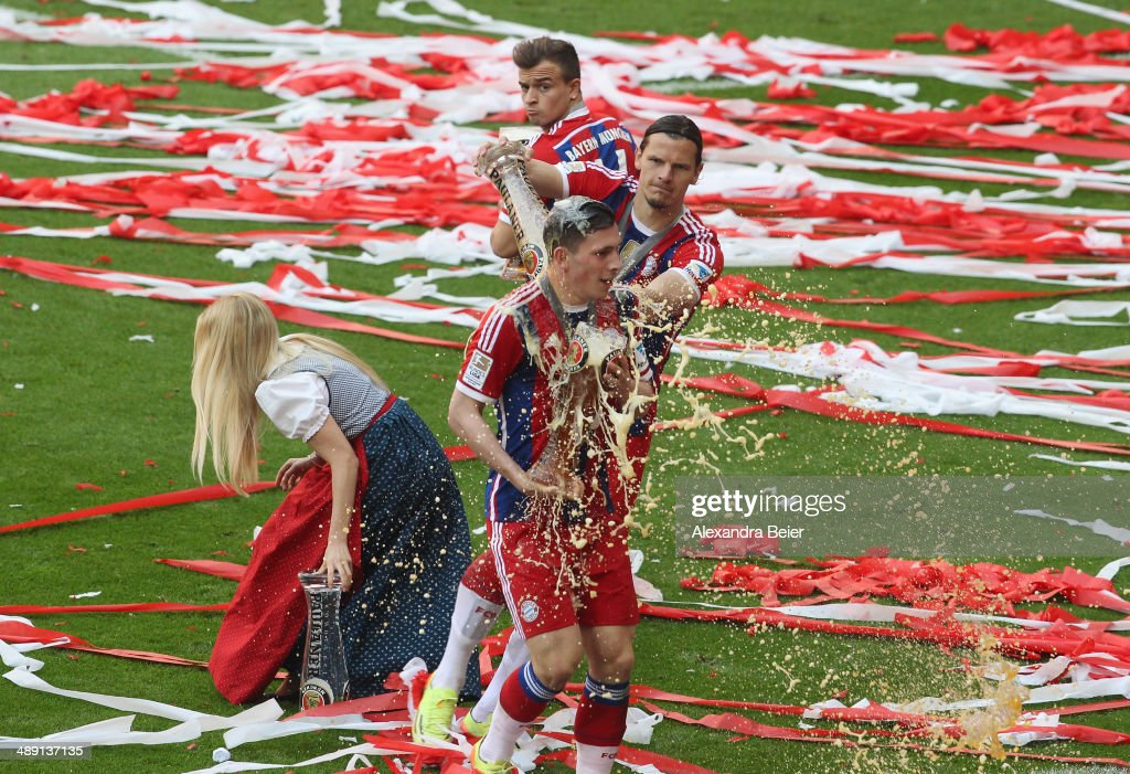Pierre-Emile Hojbjerg of Bayern Muenchen is showered with beer by <a gi-track='captionPersonalityLinkClicked' href=/galleries/search?phrase=Daniel+van+Buyten&family=editorial&specificpeople=213252 ng-click='$event.stopPropagation()'>Daniel van Buyten</a> to celebrate winning the German Bundesliga Championship after the Bundesliga match between FC Bayern Muenchen and VfB Stuttgart at Allianz Arena on May 10, 2014 in Munich, Germany.