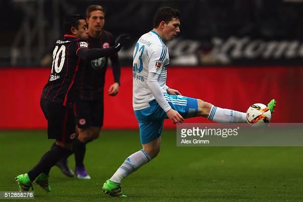 PierreEmile Hojbjerg of Schalke is challenged by Marco Fabian of Frankfurt during the Bundesliga match between Eintracht Frankfurt and FC Schalke 04...