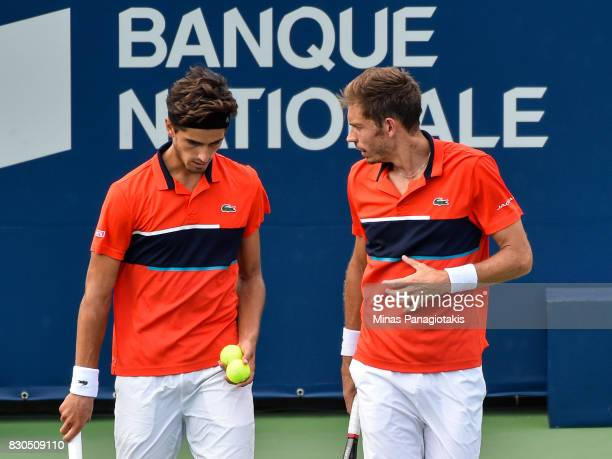 PierreHugues Herbert and teammate Nicolas Mahut of France discuss their strategy in a doubles match against Mike and Bob Bryan of the United States...