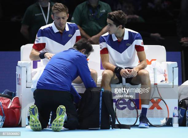 PierreHugues Herbert with an injured Nicolas Mahut of France against JeanJulien Rojer of Netherlands and Horia Tecau of Romania in the doubles during...