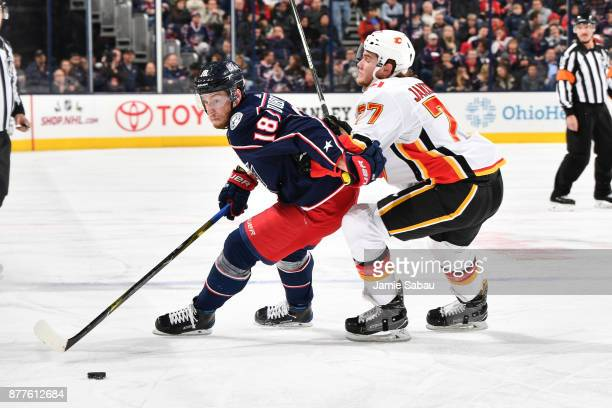 PierreLuc Dubois of the Columbus Blue Jackets attempts to skate the puck away from Mark Jankowski of the Calgary Flames during the third period of a...