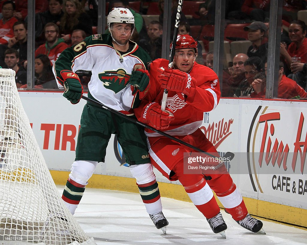 Pierre-Marc Bouchard #96 of the Minnesota Wild and Brendan Smith #2 of the Detroit Red Wings battle for position behind the net during a NHL game at Joe Louis Arena on March 20, 2013 in Detroit, Michigan.