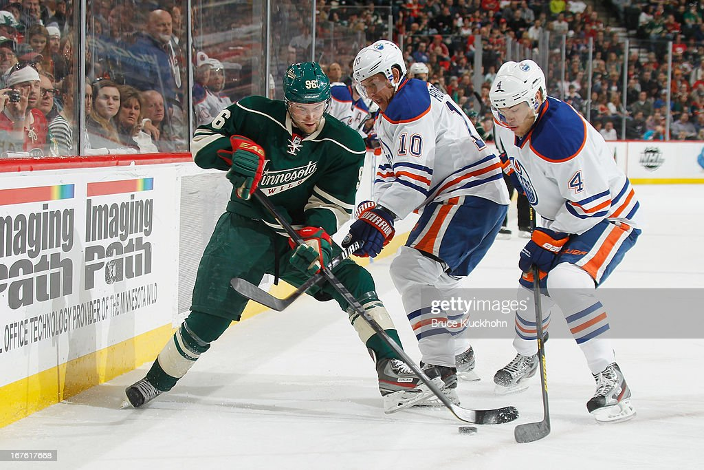 Pierre-Marc Bouchard #96 of the Minnesota Wild battles for the puck with (L-R) <a gi-track='captionPersonalityLinkClicked' href=/galleries/search?phrase=Shawn+Horcoff&family=editorial&specificpeople=239536 ng-click='$event.stopPropagation()'>Shawn Horcoff</a> #10 and <a gi-track='captionPersonalityLinkClicked' href=/galleries/search?phrase=Taylor+Hall&family=editorial&specificpeople=2808377 ng-click='$event.stopPropagation()'>Taylor Hall</a> #4 of the Edmonton Oilers during the game on April 26, 2013 at the Xcel Energy Center in St. Paul, Minnesota.