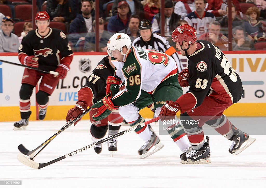 Pierre-Marc Bouchard #96 of the Minnesota Wild tries to work the puck through Raffi Torres #37 and Derek Morris #53 of the Phoenix Coyotes during the first period at Jobing.com Arena on February 4, 2013 in Glendale, Arizona.