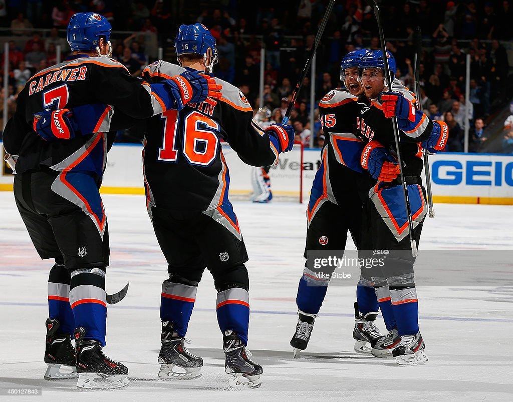 Pierre-Marc Bouchard #96 of the New York Islanders celebrates his goal with teammte Aaron Ness #55 in the second period against the Detroit Red Wings at Nassau Veterans Memorial Coliseum on November 16, 2013 in Uniondale, New York.
