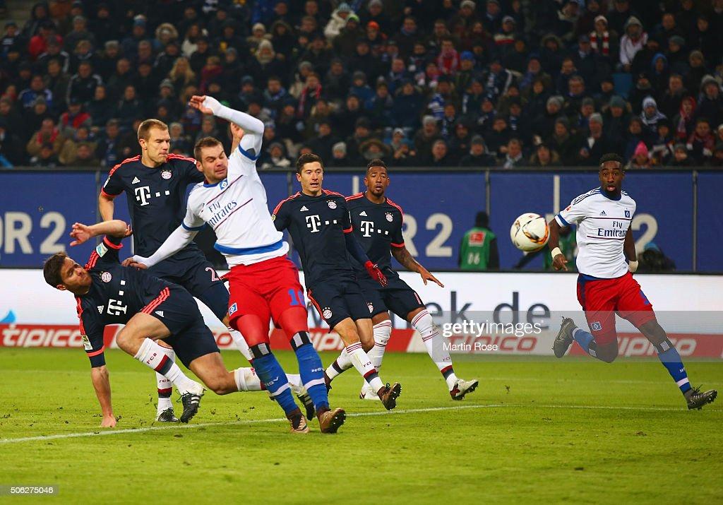 PierreMichel Lasogga of SV Hamburg challenges as Xabi Alonso of Bayern Munich scores an own goal for their equaliser during the Bundesliga match...