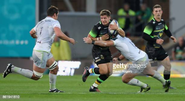 Piers Francis of Northampton is tackled by Brad Barritt and Calum Clark during the European Rugby Champions Cup match between Northampton Saints and...