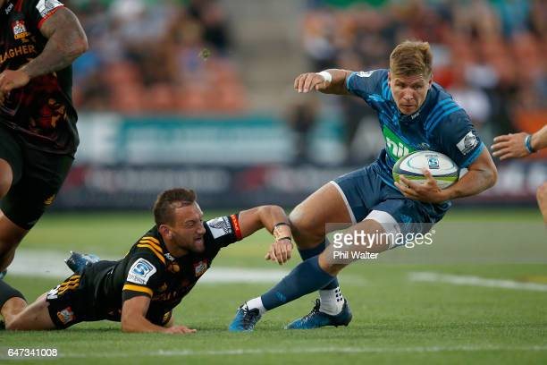 Piers Francis of the Blues is tackled by Aaron Cruden of the Chiefs during the round two Super Rugby match between the Chiefs and the Blues at Rugby...