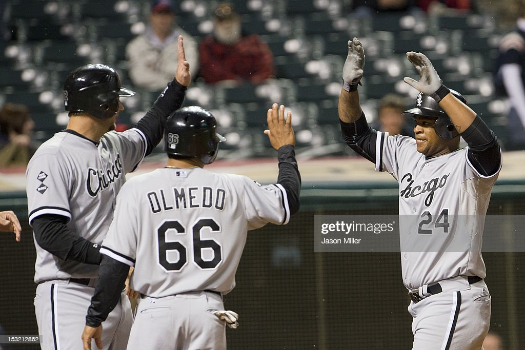 A.J. Pierzynski #12 and Ray Olmedo #66 celebrate with Dayan Viciedo #24 of the Chicago White Sox after Viciedo hit a grand slam during the ninth inning against the Cleveland Indians at Progressive Field on October 1, 2012 in Cleveland, Ohio.
