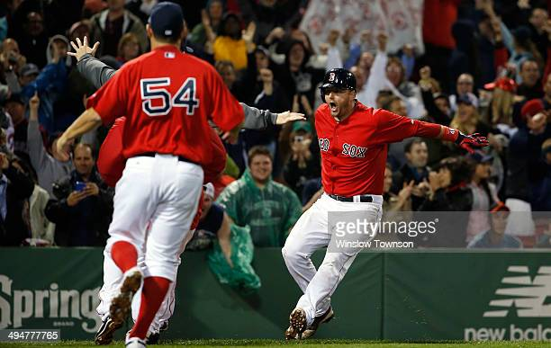 AJ Pierzynski of the Boston Red Sox is greeted by teammates after his gamewinning RBI triple during the tenth inning of their 32 win over the Tampa...