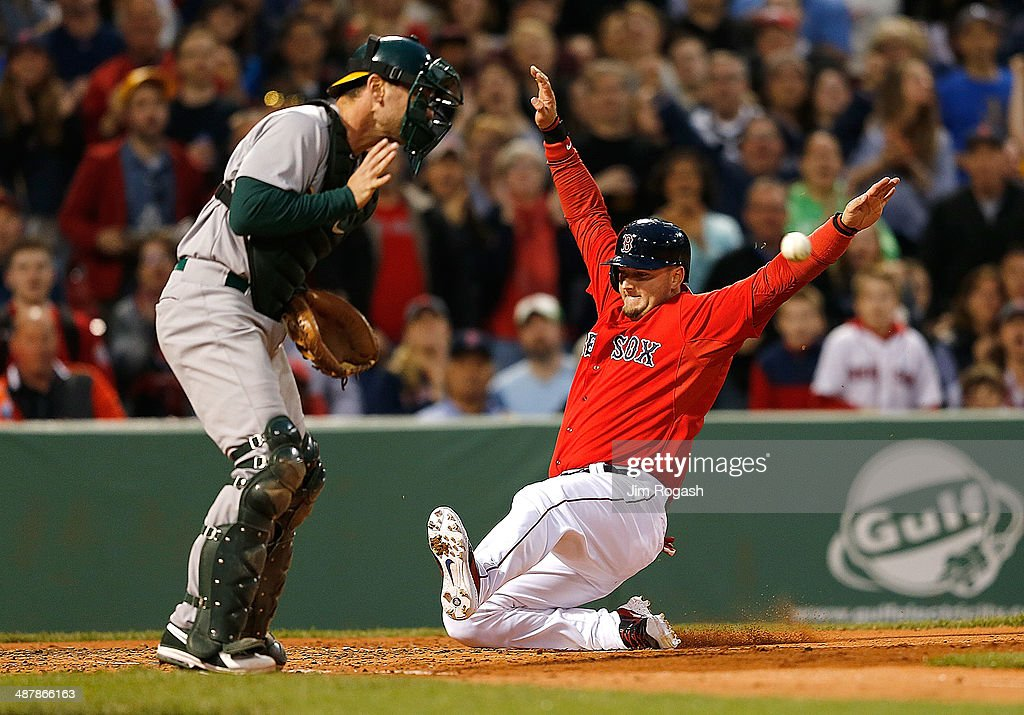 J Pierzynski of the Boston Red Sox slides home as John Jaso of the Oakland Athletics fields a late throw in the second inning at Fenway Park on May 2...
