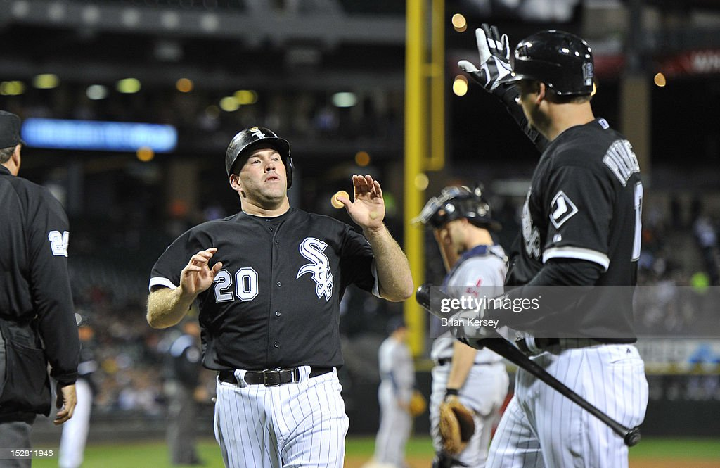 A.J. Pierzynski #12 of the Chicago White Sox (R) high-fives Kevin Youkilis #20 after he scored on a sacrifice fly hit by teammate Alex Rios #51 during the first inning against the Cleveland Indians at U.S. Cellular Field on September 26, 2012 in Chicago, Illinois.