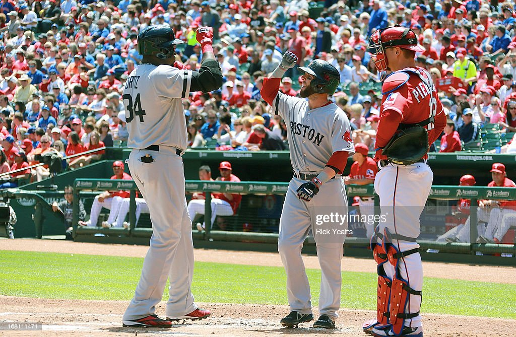 A.J. Pierzynski #12 of the Texas Rangers looks on as David Ortiz #34 is congratulated by Dustin Pedroia #15 of the Boston Red Sox for a one run home run against the Texas Rangers at Rangers Ballpark in Arlington on May 5, 2013 in Arlington, Texas.
