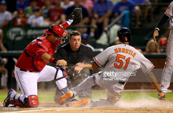 J Pierzynski of the Texas Rangers makes the out at homeplate against Henry Urrutia of the Baltimore Orioles at Rangers Ballpark in Arlington on July...