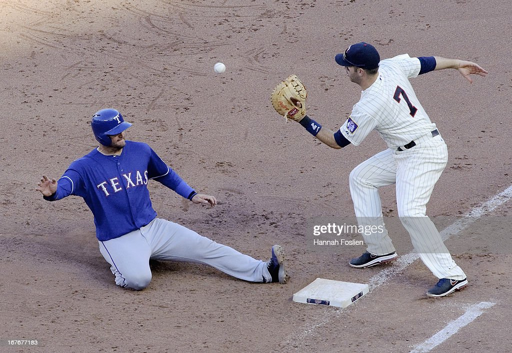 A.J. Pierzynski #12 of the Texas Rangers slides safely back to first base as Joe Mauer #7 of the Minnesota Twins catches the ball during the ninth inning of the game on April 27, 2013 at Target Field in Minneapolis, Minnesota. The Twins defeated the Rangers 7-2.