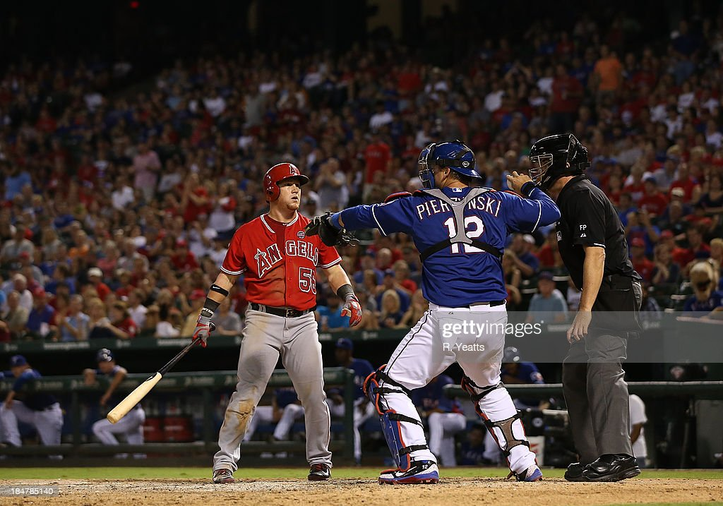 A.J. Pierzynski #12 of the Texas Rangers throws the ball back to the pitcher as Kole Calhoun #56 of the Los Angeles Angels of Anaheim reacts to a call by Mike DiMuro #16 home plate umpire at Rangers Ballpark on September 27, 2013 in Arlington, Texas.