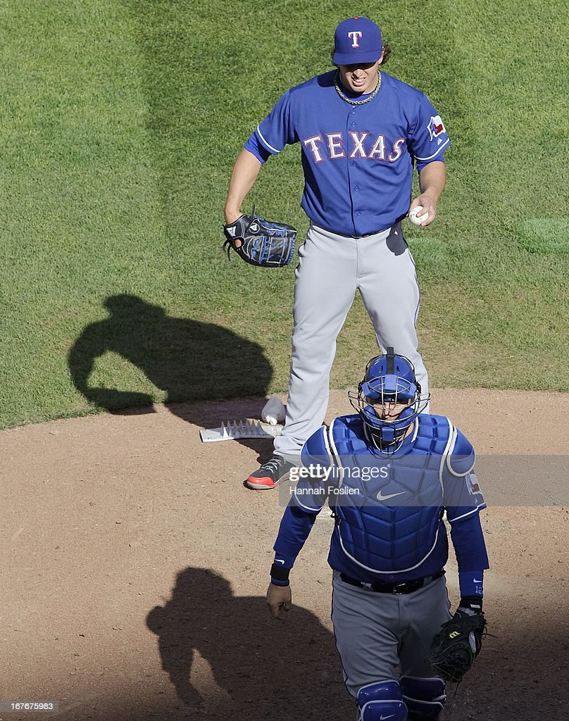 A.J. Pierzynski #12 of the Texas Rangers walks off the mound after speaking with Derek Holland #45 of the Texas Rangers during the sixth inning of the game against the Minnesota Twins on April 27, 2013 at Target Field in Minneapolis, Minnesota. The Twins defeated the Rangers 7-2.