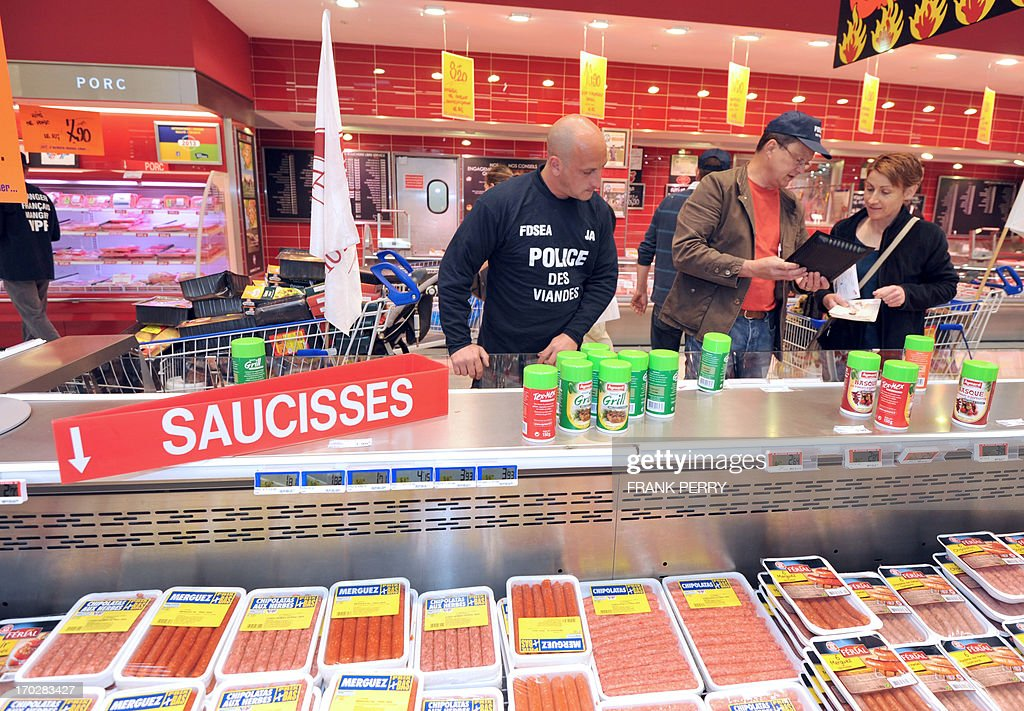Pig and poultry farmers, members of the French FNSEA union, speak with a custumer as they remove food in a Leclerc supermarket to protest against meat from foreign countries on June 10, 2013 in Saint-Herblain, near Nantes.