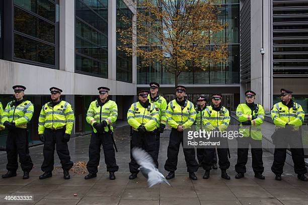 A pigeon flies in front of police officers standing outside the Home Office during a protest against education cuts and tuition fees on November 4...