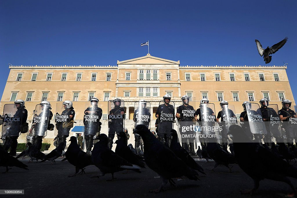 A pigeon flies over riot policemen during an anti-austerity demonstration in the center of Athens on May 6, 2010. Riot police charged hundreds of youths in front of the Greek parliament after an anti-austerity demonstration by more than 10,000 people. After a long face-off, police also used tear gas to disperse the youths who had lingered on taunting officers with insults and throwing things after the demonstration.