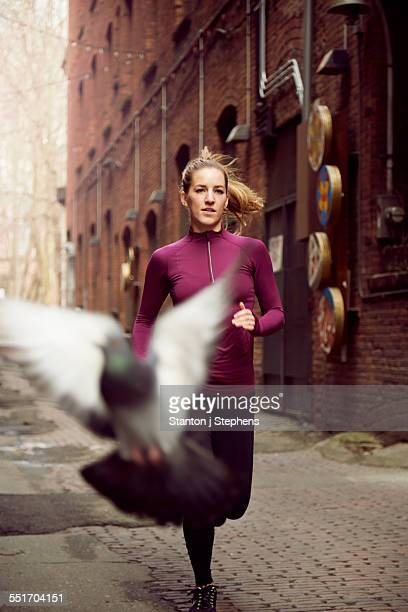 Pigeon flying in front of young female runner in alleyway