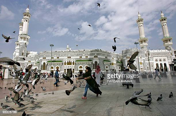 Pigeons fly as a Saudi girl runs outside alHaram mosque in Mecca 05 February 2006 Palestinian leader Mahmud Abbas and Hamas supremo Khaled Meshaal...