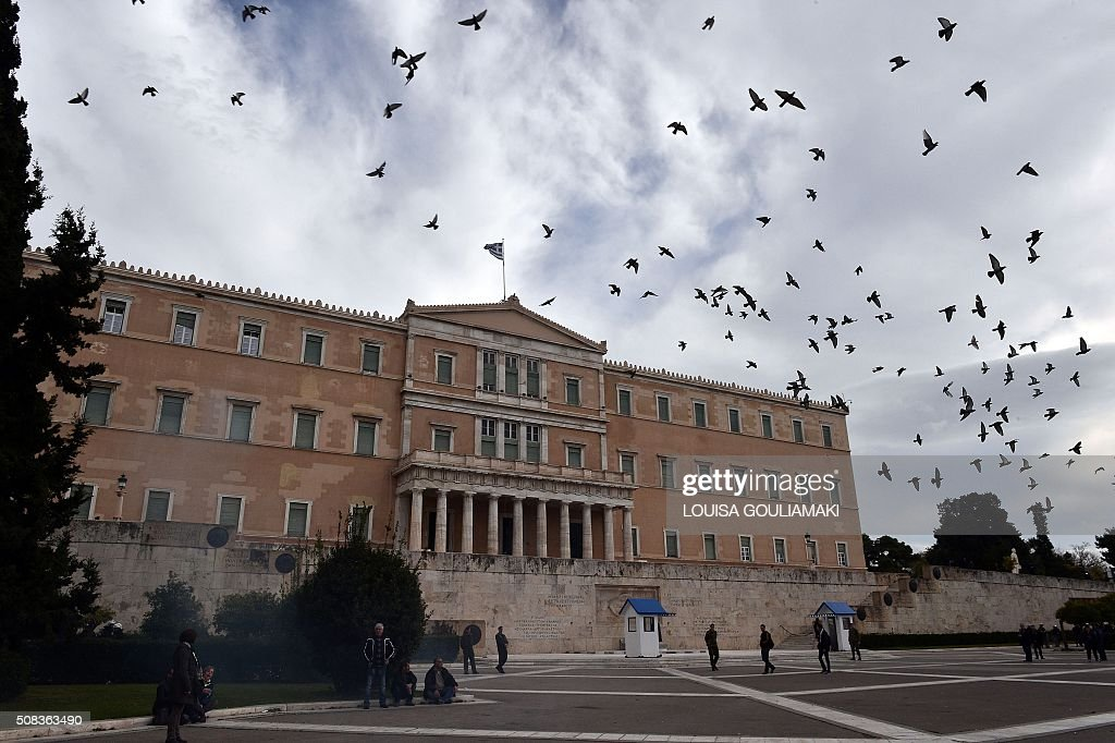 TOPSHOT - Pigeons fly in front of the Greek parliament in central Athens , as demonstrators threw a flare on February 4, 2016. GOULIAMAKI