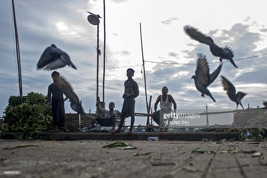 Pigeons take flight as Myanmar workers rest during sunset at a banana market in Yangon on May 31, 2016. Myanmar's growth rate, once one of the world's most impressive, has dipped following heavy floods and an investment slowdown sparked by uncertainty over its political transition, the World Bank said on May 31. / AFP / YE