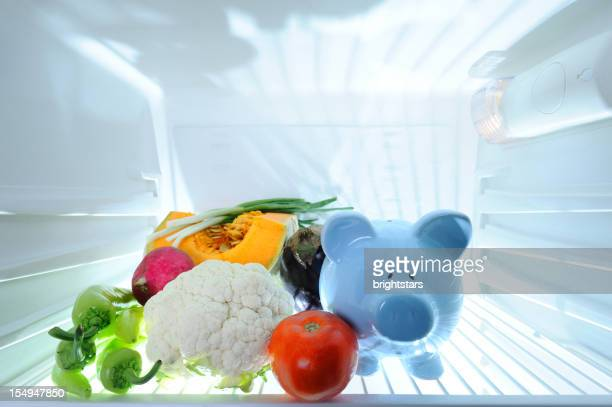 Piggy bank and vegetables in refrigerator