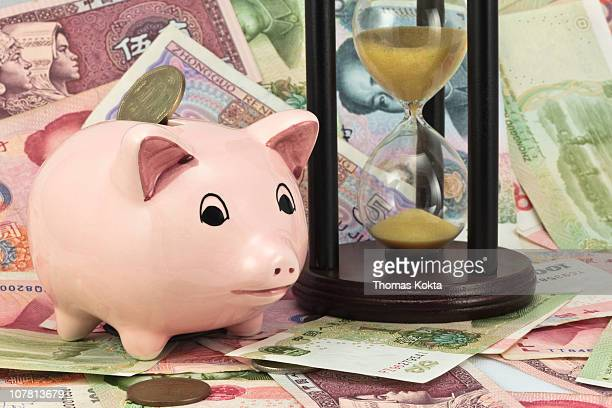 Piggy bank, currency and an hourglass