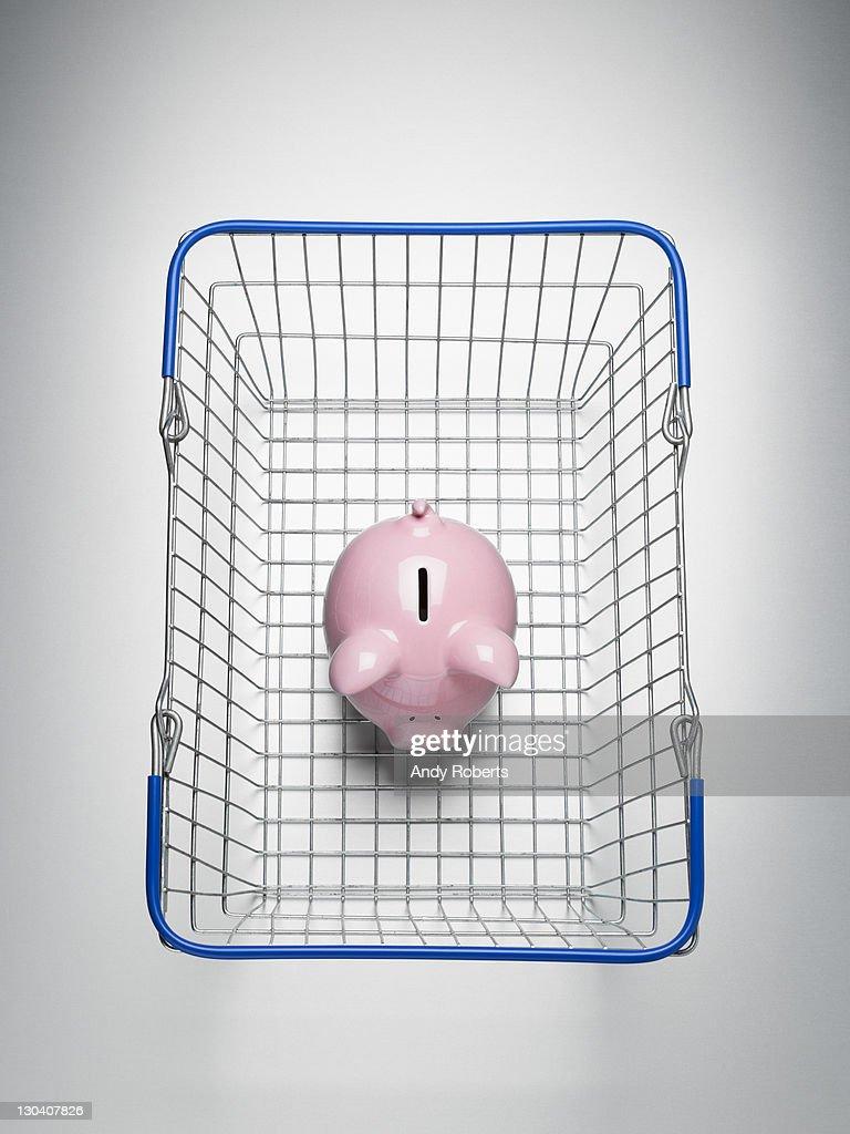 Piggy bank in shopping basket