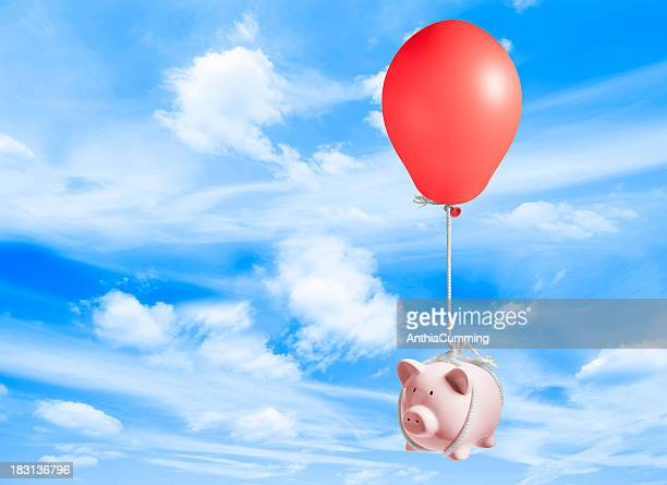 Piggy bank lifted up into sky by inflated balloon