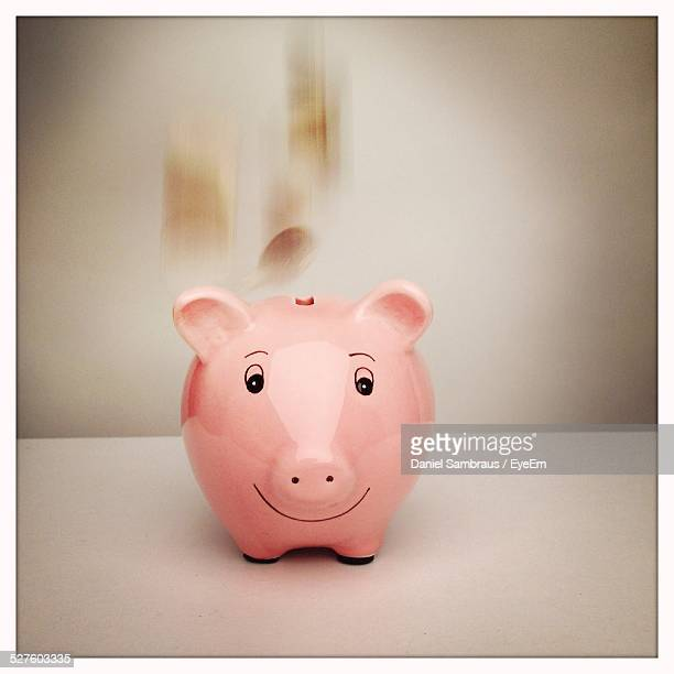 Piggy Bank On Table Against Wall