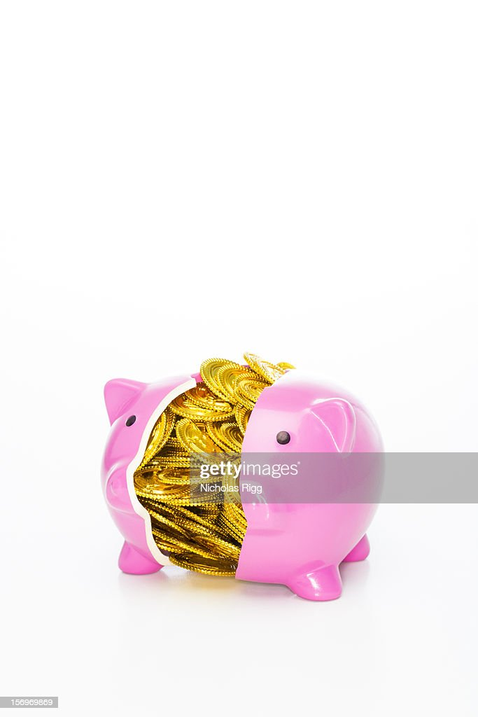 Piggy bank split in half with toy gold coins : Stock Photo