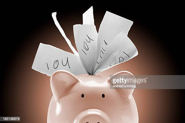 Piggy bank stuffed full of IOU notes on pink background