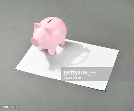 Piggy bank with a car shaped shadow : Stock Photo