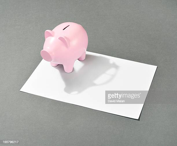 Piggy bank with a car shaped shadow