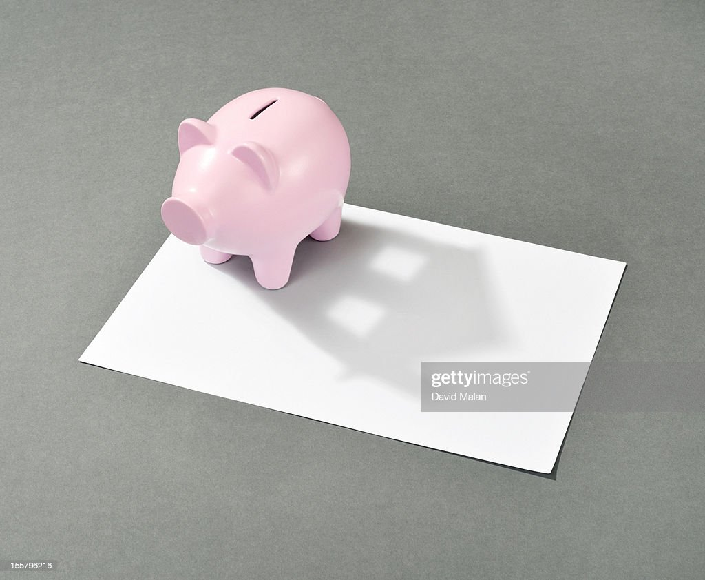 Piggy bank with a house shaped shadow