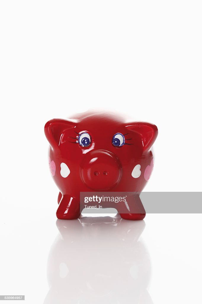 Piggy bank with heart shaped ornaments on white background : Stock Photo