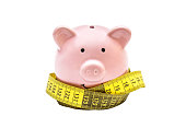 Piggy bank with measure tape on white background.