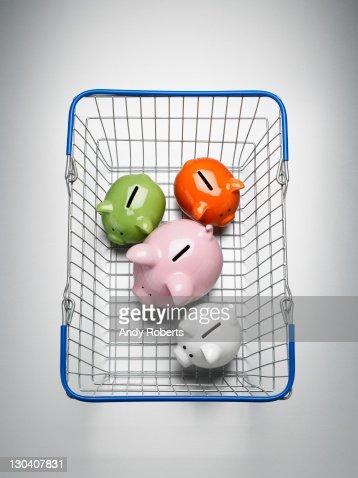 Piggy banks in shopping basket : Stock Photo