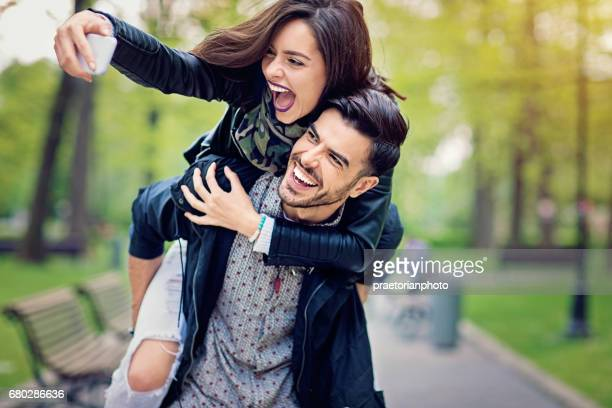 Piggyback couple is taking selfie in the park