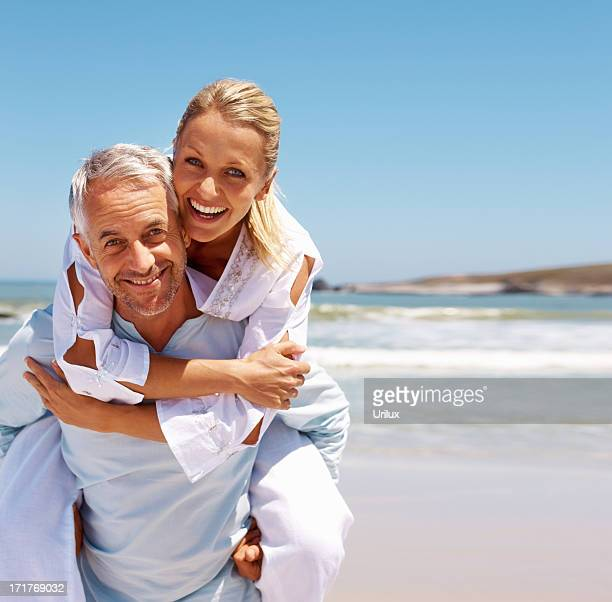 Piggybacking: Mature couple in a playful mood by the beach