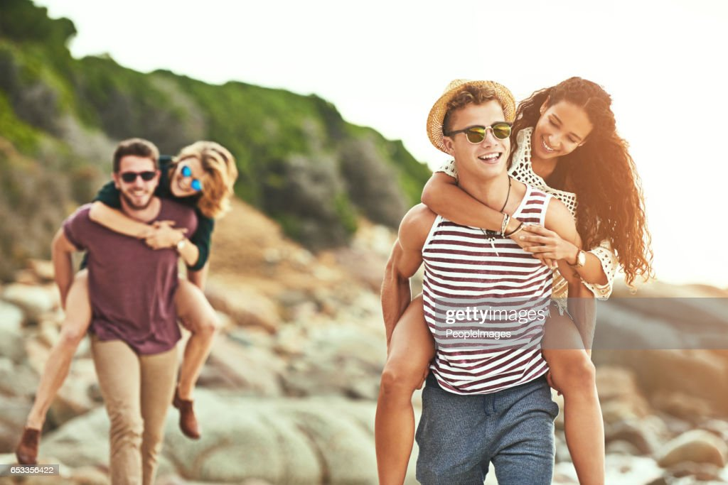 Piggybacking their girls on the beach : Stock Photo