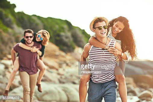 Piggybacking their girls on the beach : Stockfoto