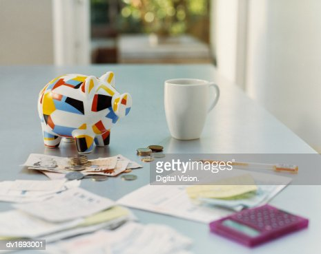 Piggybank, British Currency, Calculator, Receipts and a Mug on a Table : Stock-Foto