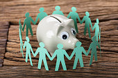 Closeup of piggybank surrounded by paper people holding hands on wooden table