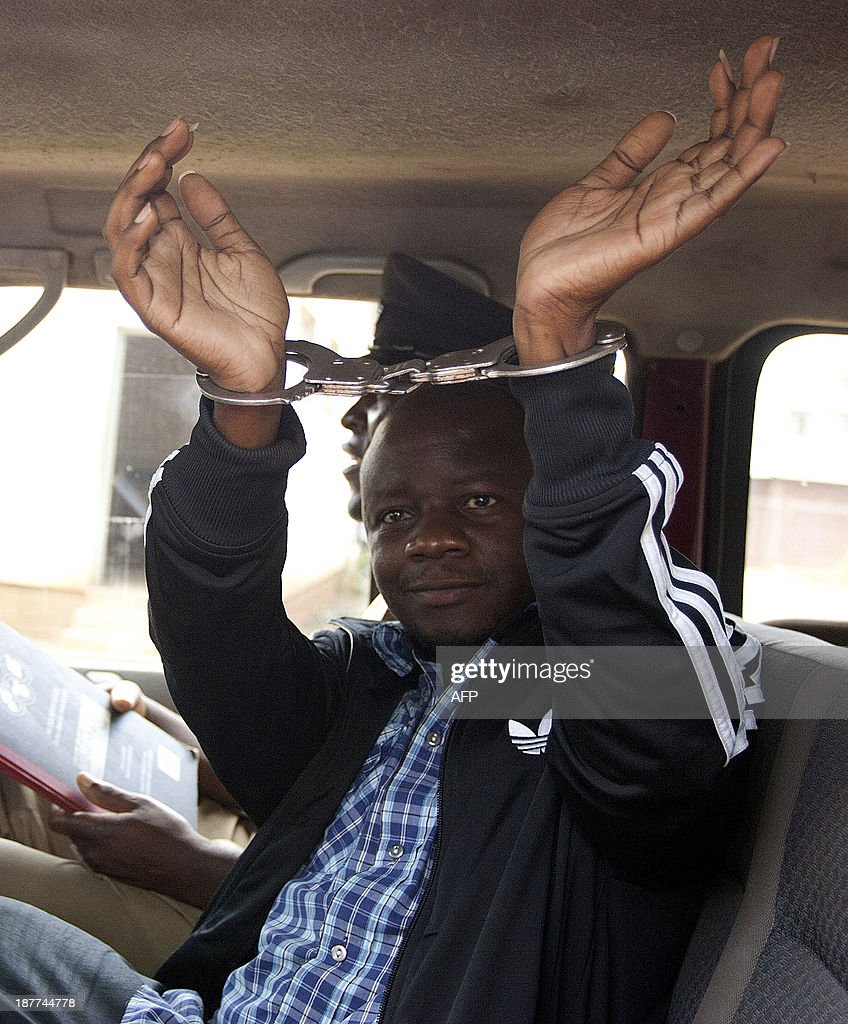 Pika Manondo, one of the suspects implicated in the shooting of Malawi's Budget Director, waves his handcuffed hands as he leaves the Lilongwe Chief Resident Magistrate Court in a police vehicle, on November 11, 2013. Malawi police said on November 8 they had arrested axed justice minister Ralph Kasambara over a failed assassination attempt on a corruption-busting treasury official. Paul Mphwiyo, the budget director in the finance ministry, was shot and wounded outside his house in September just as he was about to expose a government corruption ring. The former justice minister is the fourth suspect to be arrested over the assassination attempt. AFP PHOTO / AMOS GUMULIRA