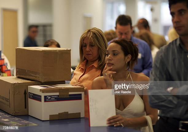 Pilar Cruz and Rose Martinez wait in a line to mail their Christmas letters and gifts at a post office December 18 2006 in Coral Gables Florida...
