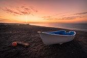 Barca en una playa mientras amanece de una forma muy particular, con un pilar de sol tras las montañas. A veces, cuando el sol está a punto de ponerse, acaba de salir o se encuentra ligeramente por de